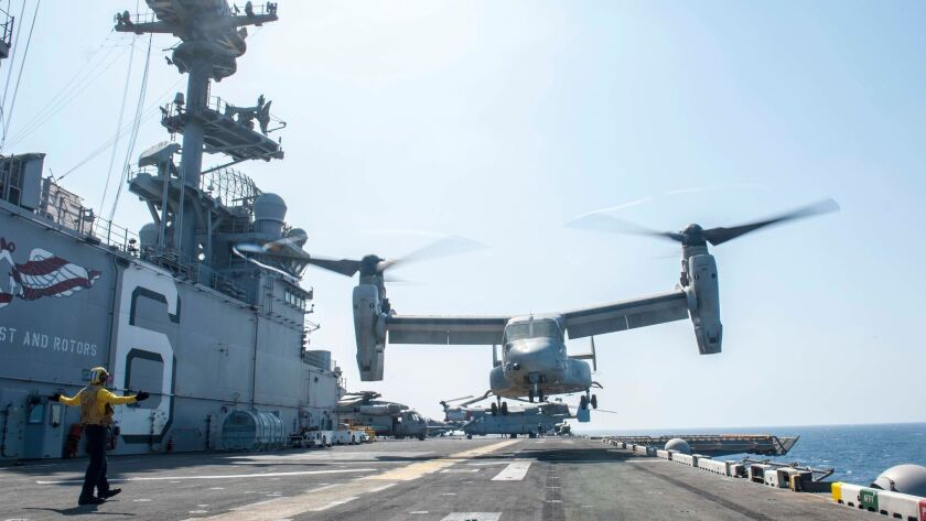 Aviation Boatswain's Mate (Handling) Airman Anthony Pinto signals an MV-22 Osprey to depart the deck of the amphibious warship America during flight operations on Oct. 24 in the Gulf of Aden. The Navy wants to swap out its C-2A Greyhound planes for the tilt-rotor Ospreys.
