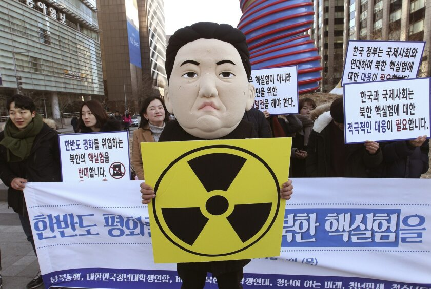 """A South Korean university student wearing a mask depicting North Korean leader Kim Jong Un participates in a rally against North Korea's announcement that it had tested a hydrogen bomb in Seoul, South Korea, Thursday, Jan. 7, 2016. North Korea's declaration that it had tested a hydrogen bomb for the first time was greeted with widespread condemnation - but also skepticism - as world powers vowed Wednesday to punish the impoverished and defiant nation with new international sanctions. The banners read """" We denounce North Korea' nuclear test."""" (AP Photo/Ahn Young-joon)"""