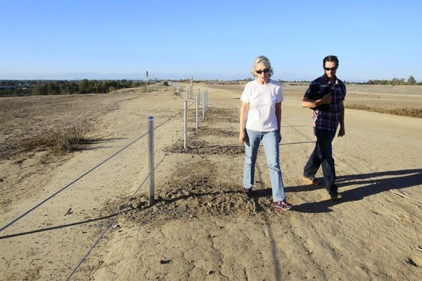 Archaeologists Patricia Martz, a professor emeritus at Cal State Los Angeles, left, and Sylvere Valentin walk in Fairview Park on Monday. Both are with the California Cultural Resources Preservation Alliance and feel a planned turnaround in the park will disrupt the Fairview Indian Site, which has been listed on the National Register of Historic Places since 1972.
