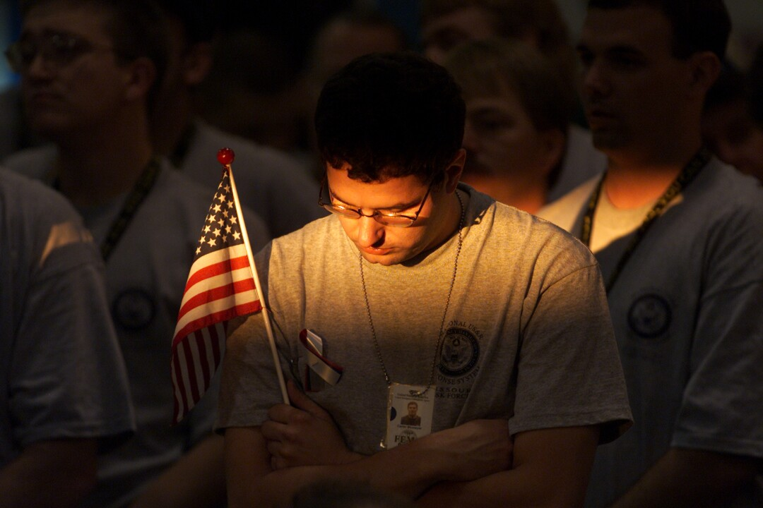 A man holds a small U.S. flag and bows his head