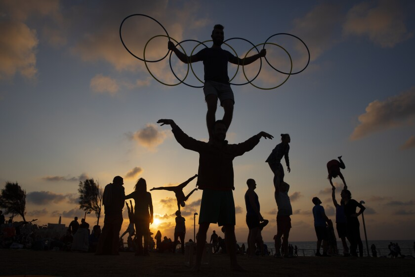 Acrobats perform gymnastic stunts as they work out during a nationwide lockdown to curb the spread of the COVID-19 virus at a park in Tel Aviv, Israel, Saturday, Feb. 6, 2021. (AP Photo/Oded Balilty)