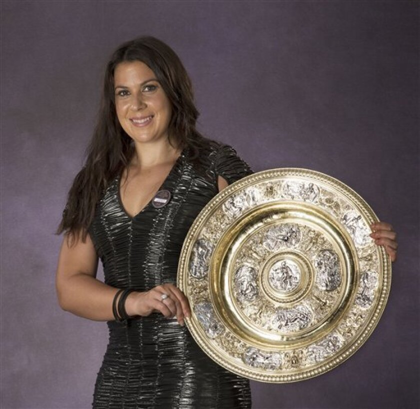 In this photo taken Sunday, July 7, 2013, the Wimbledon Women's singles 2013 tennis champion Marion Bartoli of France poses with the trophy during the Champions' Dinner at a hotel in London. (AP Photo/AELTC, Bob Martin)