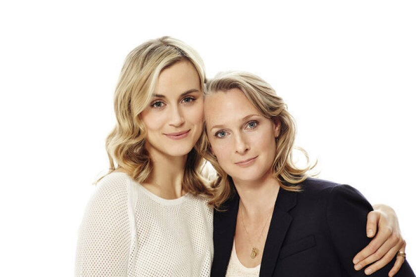 """Actress Taylor Schilling, left, poses with Piper Kerman, author of the book """"Orange Is the New Black,"""" now a Netflix series."""