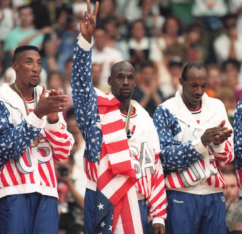 The United States' Michael Jordan, center, poses Aug. 8, 1992, with his gold medal during the Barcelona Olympics with a flag dropped over his shoulder to hide a rival sponsor's logo on his jacket.