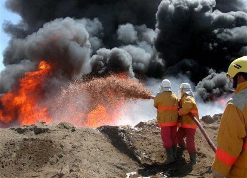 In this Sept. 14, 2004 file photo, fire fighters try to contain an oil pipeline fire after an attack by insurgents near Beiji, 250 kilometers (155 miles) north of Baghdad, Iraq. Iraq's minority Kurds are upping the ante with their go-it-alone oil policy, luring some of Big Oil's biggest players and again challenging Iraq's central government to a showdown over a shared export route. (AP Photo/Yahaya Ahmed, File)