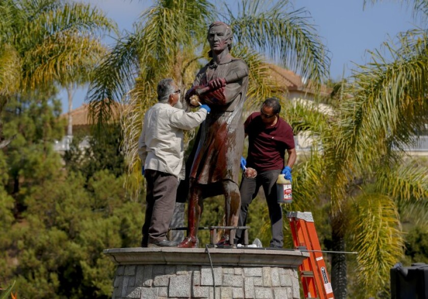 Workers clean paint off Christopher Columbus statue at Discovery Park in Chula Vista