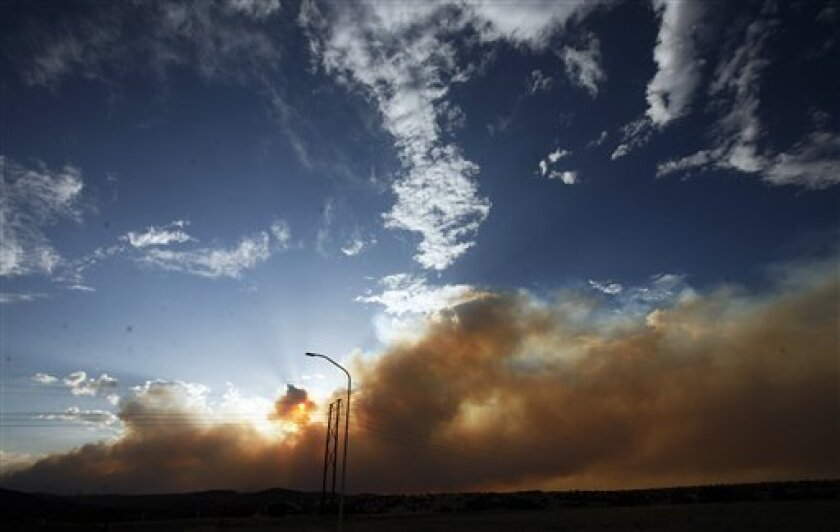 Smoke and flames from the wildfire that has threatened Los Alamos  approach Santa Clara Pueblo in New Mexico Thursday June 30, 2011.    Santa Clara Pueblo Gov. Walter Dasheno declared an emergency for the pueblo because of the damage being done by the fire.  (AP Photo/Natalie Guillén/The New Mexica