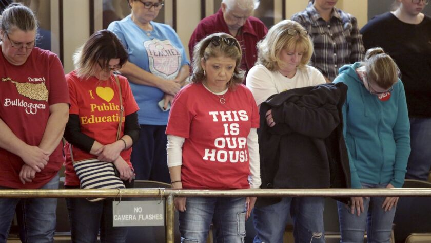 Teachers and supporters in the Senate gallery bow their heads in prayer as they protest at the Capitol in Oklahoma City on April 6.