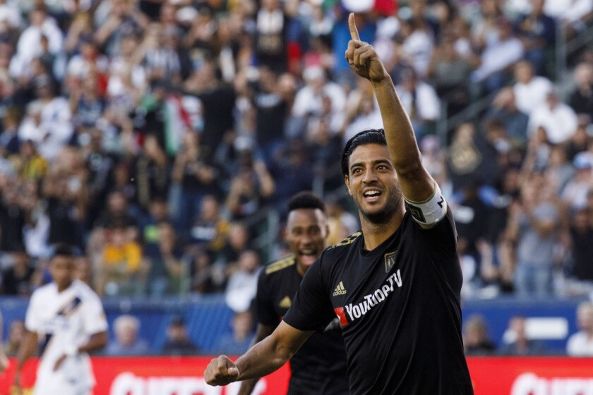 Los Angeles FC forward Carlos Vela raises a hand in celebration.