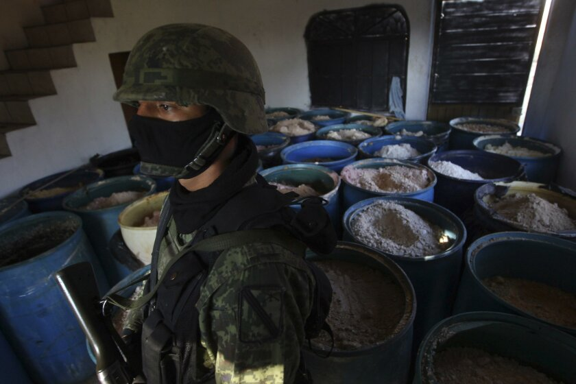 A soldier stands in a room full of barrels containing meth ingredients in Guadalajara, Mexico, in February.