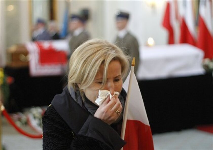 A woman weeps as Poles continue to pay their final respect to the presidential couple lying in state on Friday, April 16, 2010 in the Presidential Palace in Warsaw, Poland.  Polish President Lech Kaczynski who was killed in a plane crash in Russia is going to be buried in Krakow on Sunday.   (AP Ph