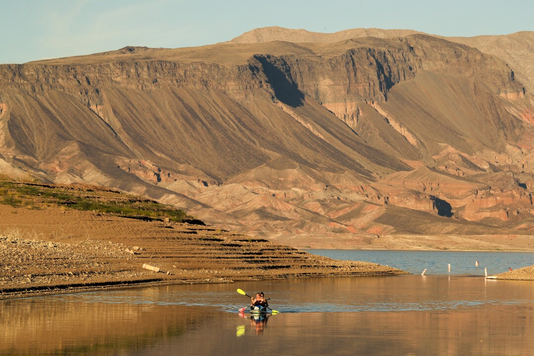 Kayakers make their way through a shallow stretch of Lake Mead