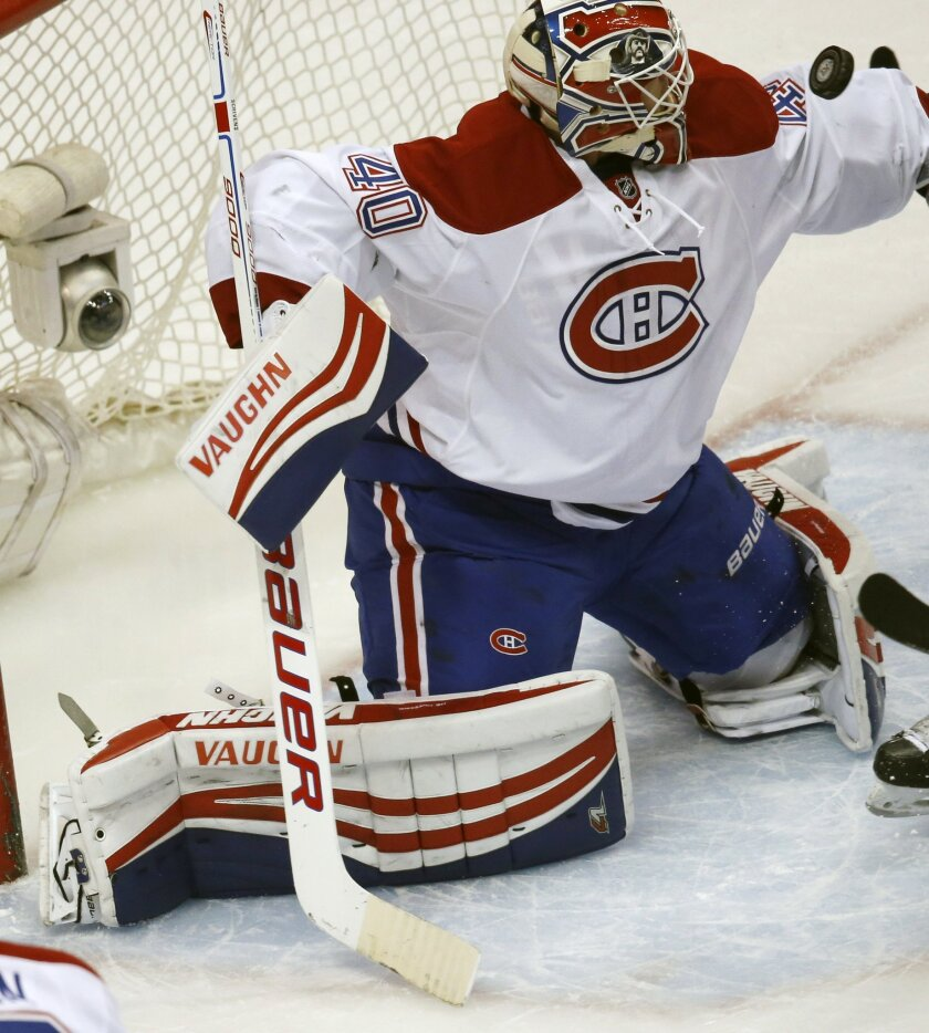 Montreal Canadiens goalie Ben Scrivens deflects a shot against the Colorado Avalanche in the first period of an NHL hockey game Wednesday, Feb. 17, 2016, in Denver. (AP Photo/David Zalubowski)