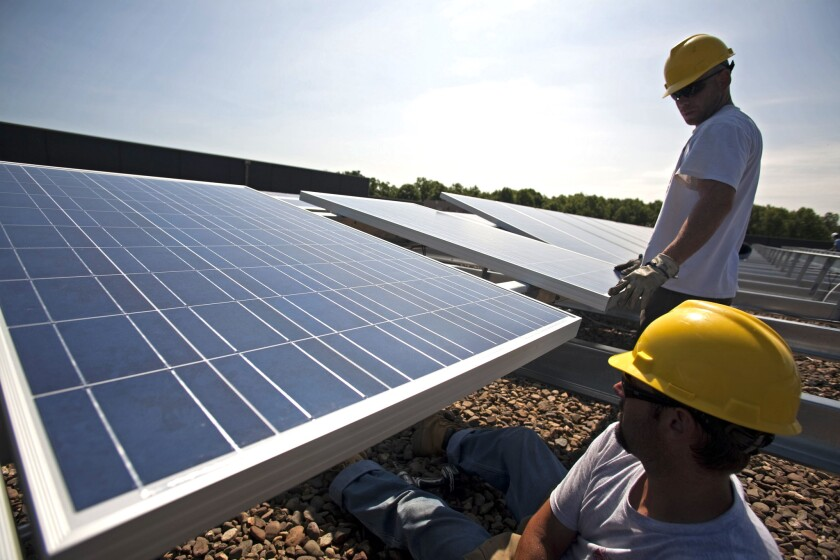 Workers install a solar array on the roof of a Kohl's Department Store in New Jersey as part of a long-term contract between the retail chain and SunEdison.