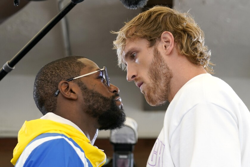 Floyd Mayweather, left, and Logan Paul pose during their news conference announcing their exhibition.