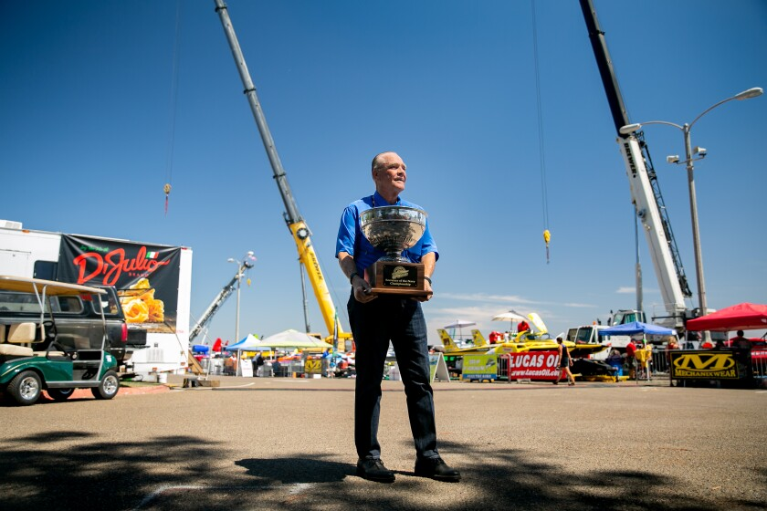 Sam Cole, president of Grand Prix World Supercharged Hydroplanes, clutches the Secretary of the Navy Cup just outside the pits Friday at Bayfair on Mission Bay.