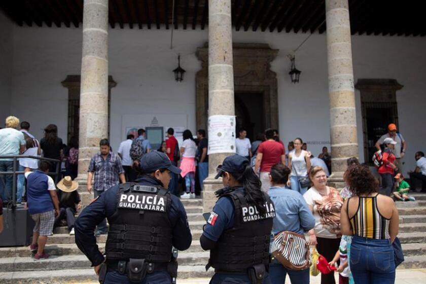 Policías custodian una casilla electoral durante la jornada electoral hoy, domingo 1 de julio de 2018, en la ciudad de Guadalajara, en el estado de Jalisco (México). La votación en las elecciones mexicanas transcurre hasta ahora en relativa calma tras una campaña marcada por el alto nivel violencia que dejó al menos 130 asesinatos, atribuidos a grupos criminales y pugnas entre partidos. EFE