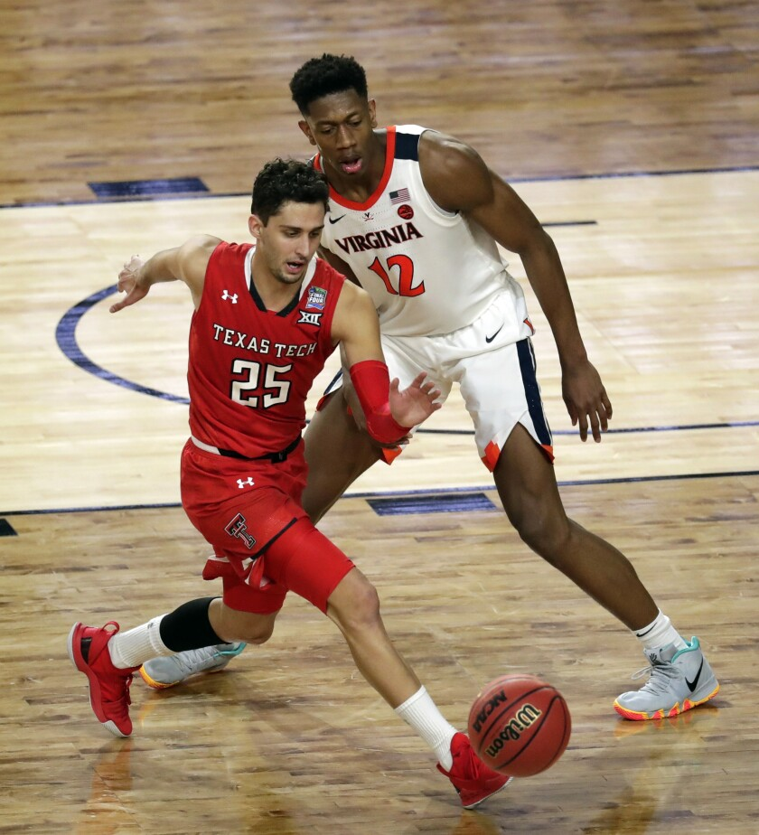 Texas Tech's Davide Moretti (25) and Virginia's De'Andre Hunter (12) chase a loose ball during the overtime in the NCAA championship championship game.