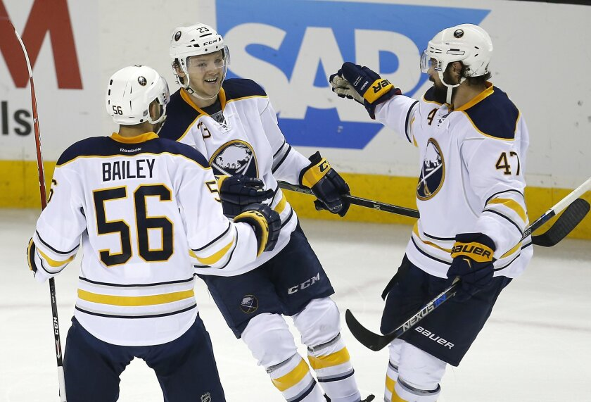 Buffalo Sabres center Sam Reinhart (23) celebrates with teammates Justin Bailey (56) and Zach Bogosian (47) after he scored a goal against the San Jose Sharks during the third period of an NHL hockey game Friday, Feb. 26, 2016, in San Jose, Calif. Buffalo won 3-1. (AP Photo/Tony Avelar)
