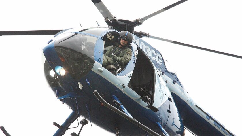 Glendale Police pilot Sean McLaughlin looks at a spotter who directs him into position to safely low