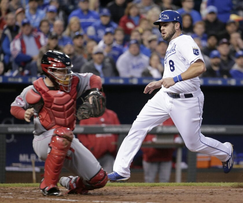 Kansas City Royals' Mike Moustakas runs past Cincinnati Reds catcher Tucker Barnhart to score on a fielders choice hit into by Eric Hosmer during the fourth inning of a baseball game Wednesday, May 20, 2015, in Kansas City, Mo. (AP Photo/Charlie Riedel)