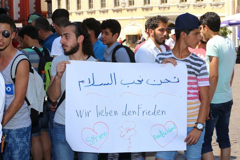Refugees, some of whom come from Syria, and their supporters demonstrate with posters written with 'we love peace'  in downtown Wuerzburg, Germany, Wednesday July 20, 2016. They are responding to the attack by a suspected Afghan refugee who attacked and critically injured passengers with an axe and