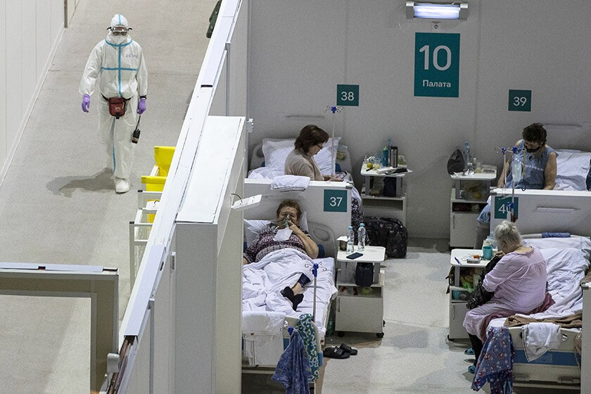 A medical worker walks near a room of four coronavirus patients at a temporary hospital in Moscow.
