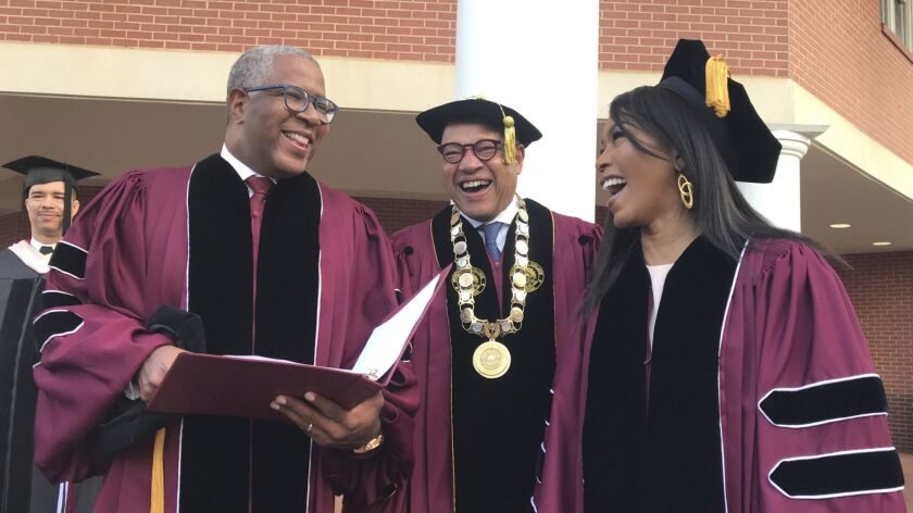 Robert F. Smith, left, laughs with David Thomas, center, and actress Angela Bassett at Morehouse Col