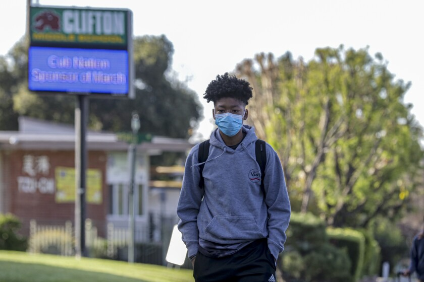 Joshua Guyton, in face mask as a precautionary measure, arrives on Thursday at Clifton Middle School in Monrovia, which was open after crews performed a deep cleaning overnight after a parent came in contact with someone exposed to the novel coronavirus.