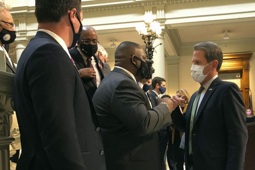 Georgia Gov. Brian Kemp, right, bumps fists with Democratic state Rep. Carl Gilliard of Garden City on Tuesday, Feb. 16, 2021, at the state Capitol in Atlanta. The Republican Kemp announced a plan to abolish Georgia's citizen's arrest law, partly blamed in the 2020 shooting death of Ahmaud Arbery near Brunswick, Ga. (AP Photo/Jeff Amy)