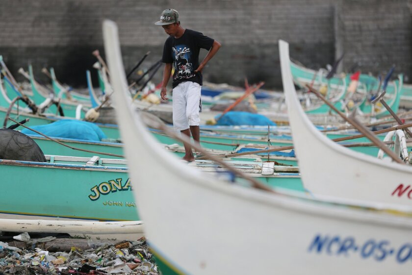 """A Filipino walks small fishing boats docked beside a coastal village of Navotas, north of Manila, Philippines as they prepare for a coming storm on Monday, July 14, 2014. The Philippines is bracing for possible floods and landslides as Tropical Storm Rammasun, locally called """"Glenda"""", intensified while moving closer to the eastern seaboard. (AP Photo/Aaron Favila)"""