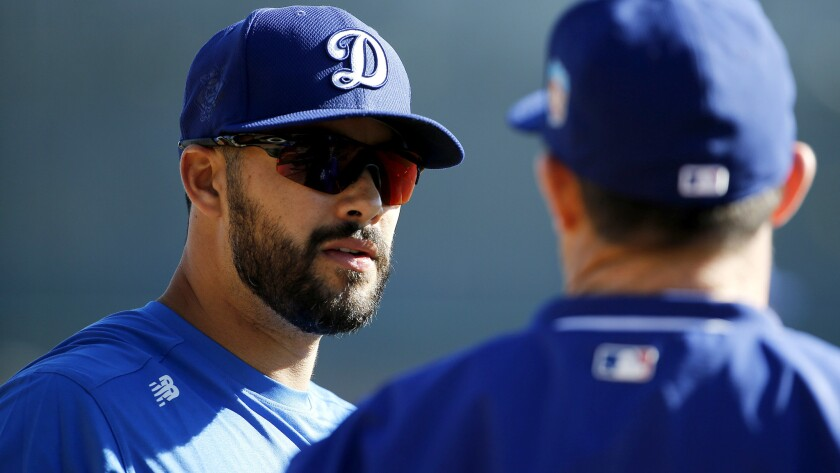 Outfielder Andre Ethier, left, talking with hitting coach Turner Ward during spring training, is back with the Dodgers after sitting out five months because of a broken leg.