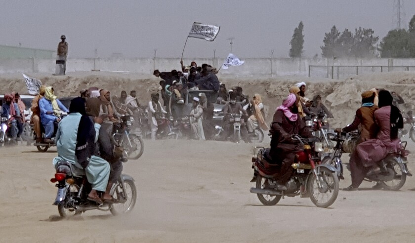 People on motorbikes gather, some holding flags