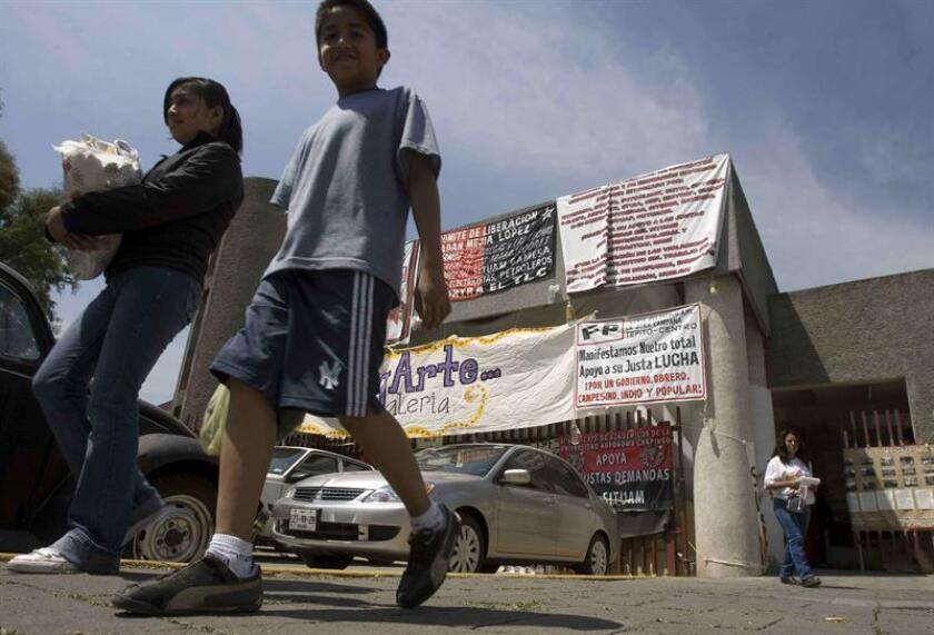Dos niños caminan frente a las instalaciones de la Universidad Autónoma Metropolitana (UAM) de Ciudad de México, EL 19 de marzo de 2008, cuando se cumplen 48 días del paro del sindicato de trabajadores de ese centro académico por un conflicto salarial, el cual afecta a 45.000 estudiantes y cerca de 5.000 trabajadores. EFE/Archivo