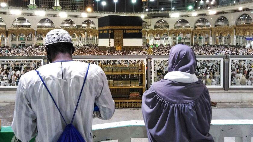 Muslim worshipers watch as others circumambulate around the Kaaba, Islam's holiest shrine, at the Grand Mosque in Saudi Arabia's holy city of Mecca on Aug. 17, 2018, prior to the start of the annual hajj pilgrimage.