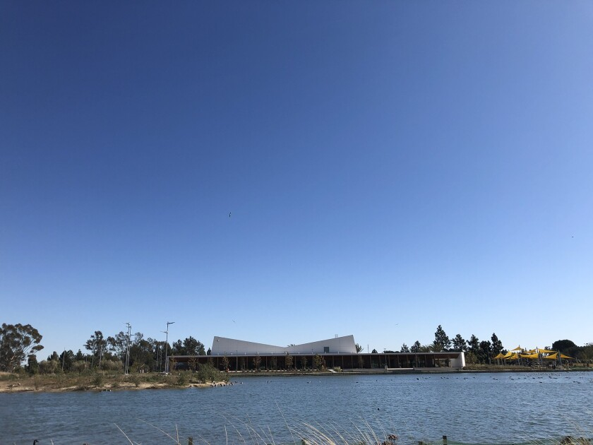 A view across a lake to a building with a tilted roofline.