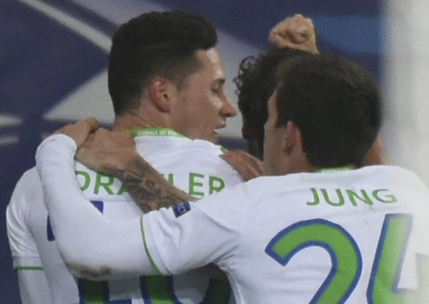 Wolfsburg's Julian Draxler, left, is hugged by his teammates after scoring his side's first goal during the Champions League round of 16, 1st leg soccer match between Gent and Wolfsburg at Ghelamco Arena in Ghent, Belgium, Wednesday, Feb. 17, 2016. (AP Photo/Geert Vanden Wijngaert)