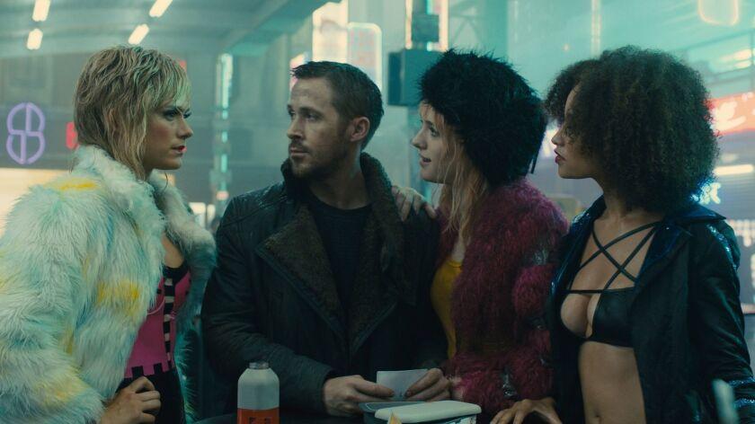"(Center L-R) Ryan Gosling as K and MacKenzie Davis as Mariette in ""Blade Runner 2049."""