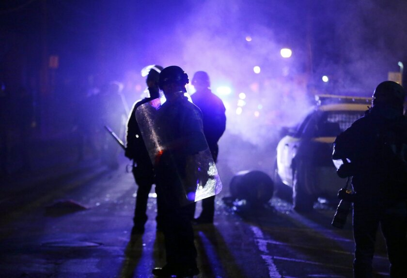 FILE - In this Nov. 25, 2014 file photo, police officers watch protesters as smoke fills the streets in Ferguson, Mo. Ferguson's cost of implementing reforms spelled out in a consent agreement with the U.S. Department of Justice could approach $4 million in the first year alone, according to new es