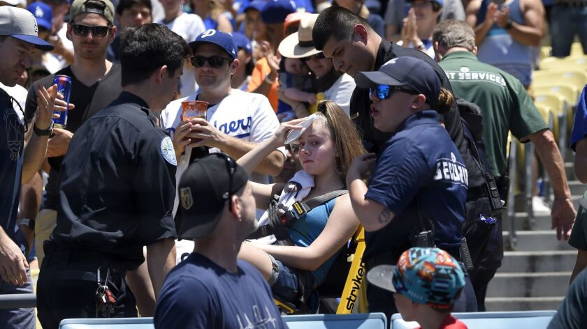 A young fan is carted away after being hit with a foul ball hit by Los Angeles Dodgers' Cody Belling