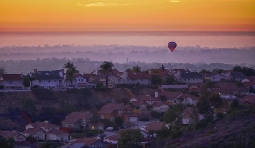 A hot air balloon flies above homes in Rancho Penasquitos