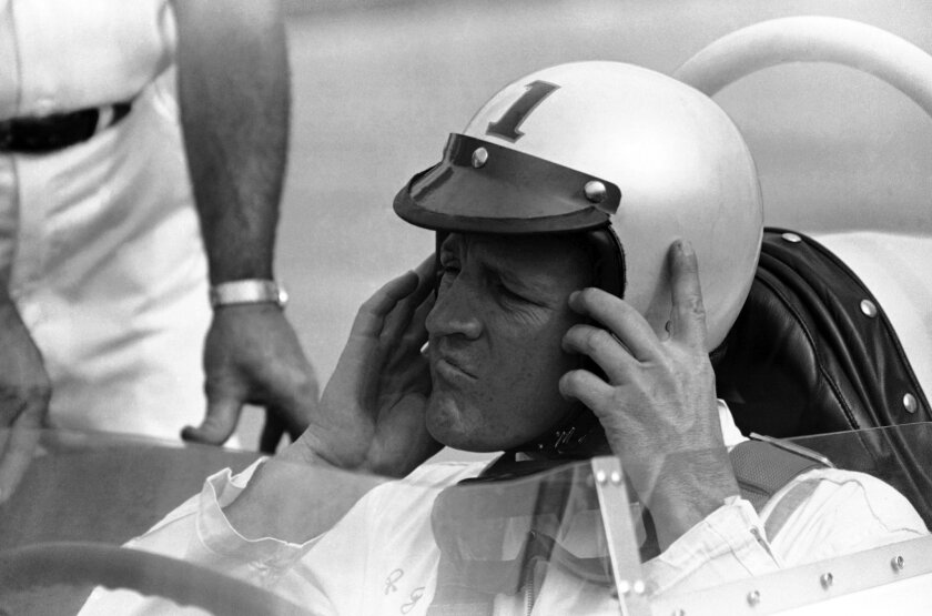 """FILE - In this May 16, 1964, file photo, A.J. Foyt removes his helmet  after qualifying for a second-row starting spot for the May 30 Indianapolis 500 auto race in Indianapolis, Ind. In the lead-up to the 100th running of the """"The Greatest Spectacle in Racing,"""" The Associated Press interviewed the"""