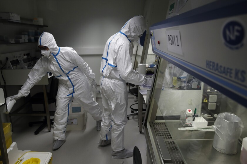 French lab scientists in hazmat gear inserting liquid in test tube manipulate potentially infected patient samples at Pasteur Institute in Paris Thursday.