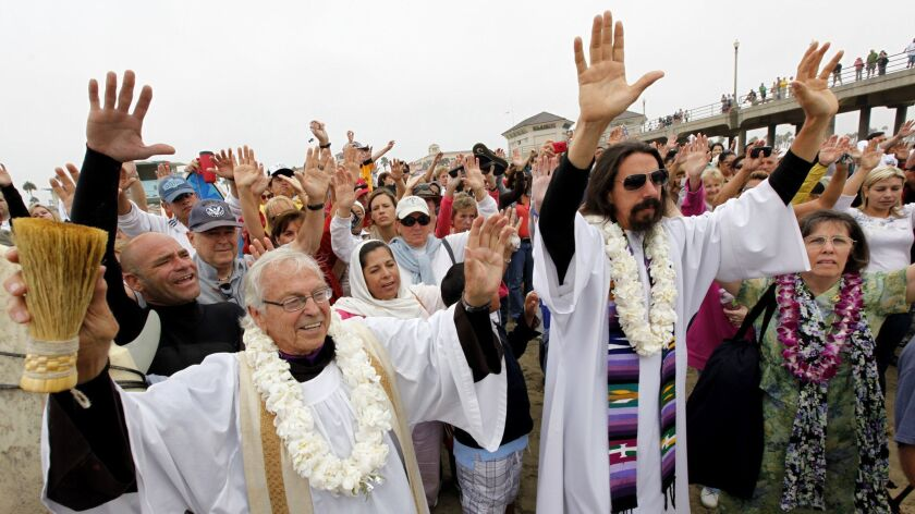 The Rev. Christian Mondor, left, and the Rev. Matthew Munoz offer a prayer during the 2010 Blessing of the Waves ceremony at the Huntington Beach Pier.