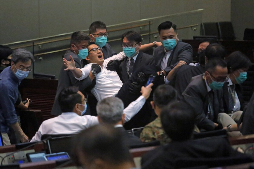 Lam Cheuk-ting, a pan-democratic legislator in Hong Kong, is taken away by security during a meeting by the legislature's House Committee on Monday.