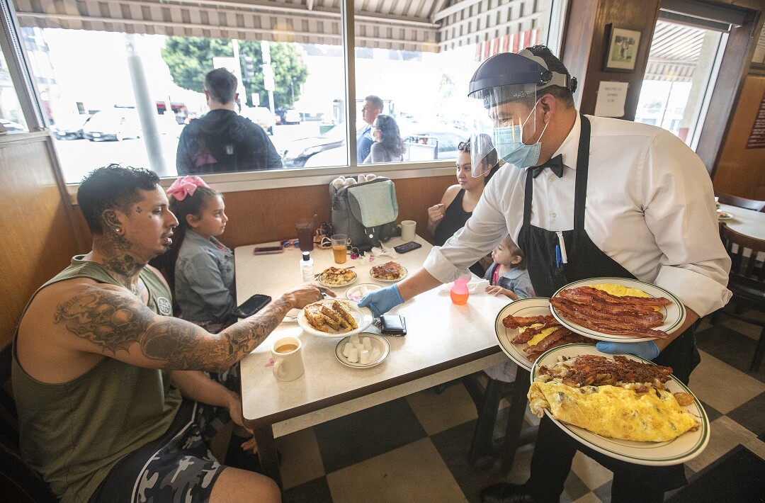 Jesus Segura, right, serves customers at the Original Pantry in downtown Los Angeles on Wednesday.