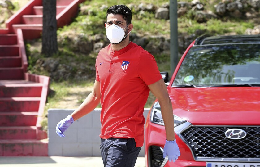 In this photo provided by Atletico Madrid, Diego Costa wearing a face mask and gloves attends the club's training ground in Madrid, Spain, on Wednesday May 6, 2020. Soccer players in Spain returned to their team's training camps Wednesday for the first time since the country entered a lockdown nearly two months ago because of the coronavirus pandemic. (Atletico Madrid via AP)
