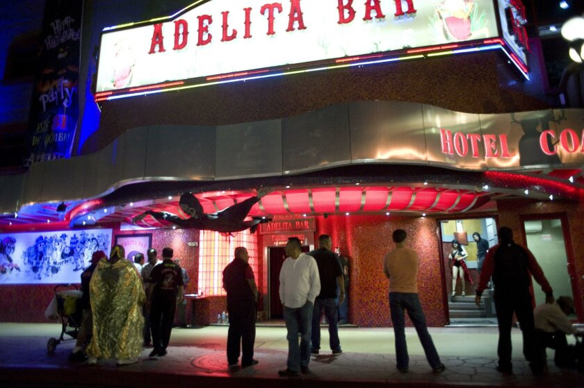 People mill about outside a strip club in Tijuana's red-light district.