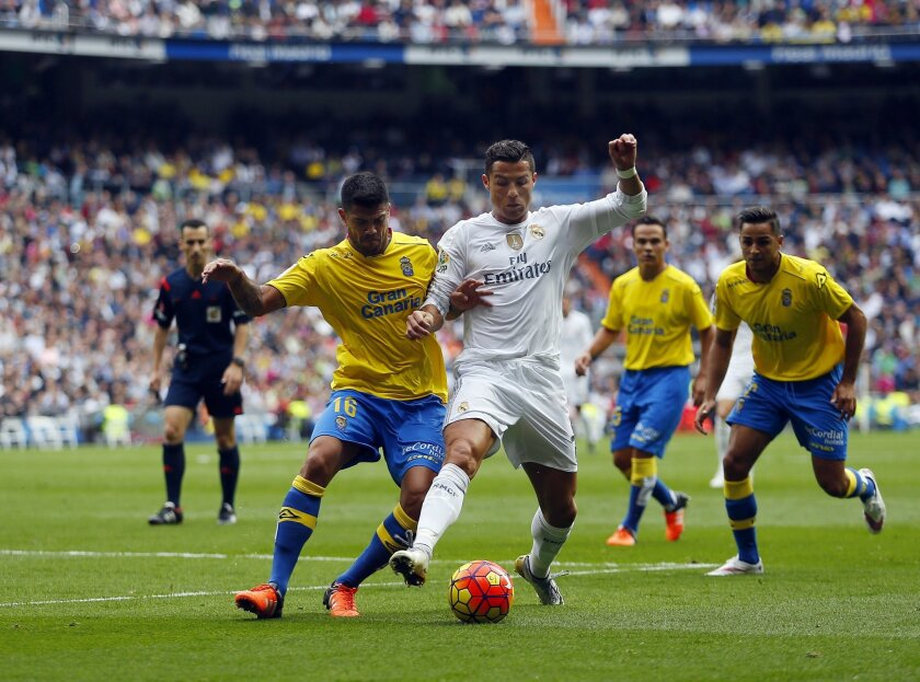 Real Madrid's Cristiano Ronaldo, right, tussles for the ball with Las Palmas' Aythami Artiles during the Spanish La Liga soccer match between Real Madrid and Las Palmas at the Santiago Bernabeu stadium in Madrid, Saturday, Oct. 31, 2015. Ronaldo scored once in Real Madrid's 3-1 victory. Ronaldo sco