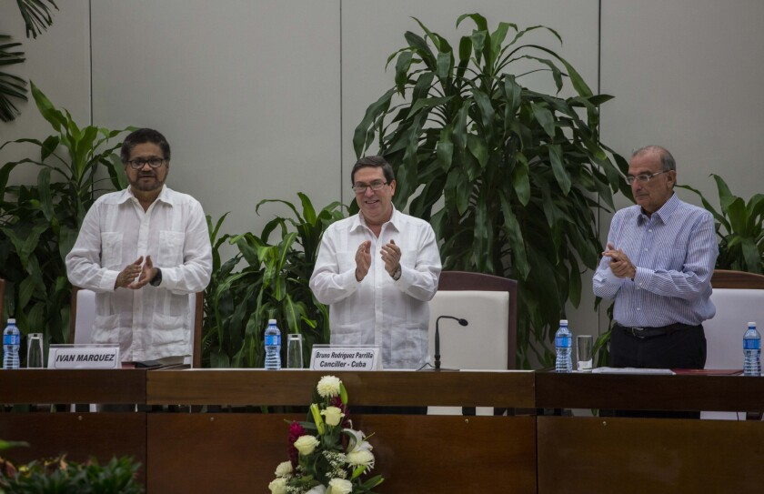 Ivan Marquez, chief negotiator of the Revolutionary Armed Forces of Colombia, or FARC, from left, Cuba's Foreign Minister Bruno Rodriguez, and Humberto de La Calle, head of Colombia's government peace negotiation team, applaud after the signing of the latest text of the peace accord between the two sides in Havana, Cuba, Saturday, Nov. 12, 2016.